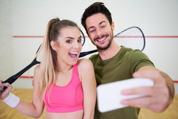Squashvrienden die een selfie maken op de baan