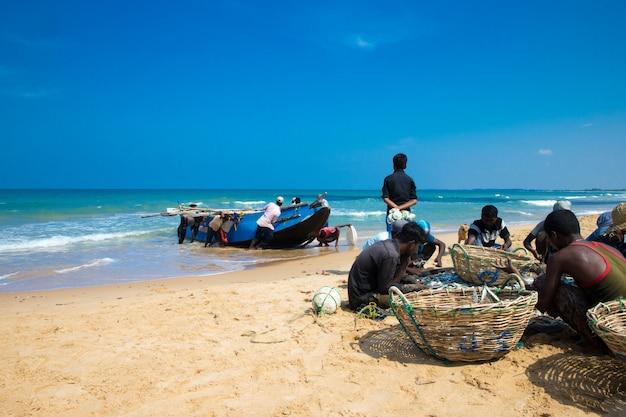 Sri lanka - 23 mach: lokale vissers trekken een visnet uit de indische oceaan op 23 mach 2017 in kosgoda, sri lanka. vissen in sri lanka is de manier waarop ze hun brood verdienen.