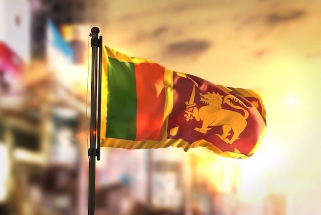 Sri lanka vlag tegen stad wazige achtergrond bij zonsopgang achtergrondverlichting