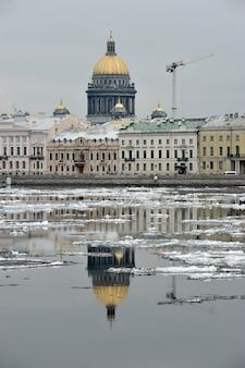 St. isaac's cathedral en de bouwkraan worden weerspiegeld in de neva-rivier in de lente, st. petersburg, rusland