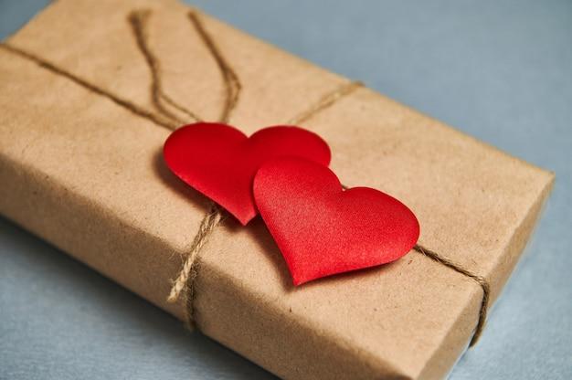 St. valentijnsdag concept. een geschenk van sint valentijnsdag in eco papier en rode harten op een grijze achtergrond