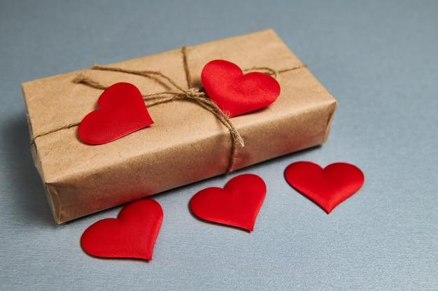 St valentijnsdag geschenkdoos verpakt in ambachtelijk papier en rode harten liggend op een grijze achtergrond. st. valentijnsdag concept.