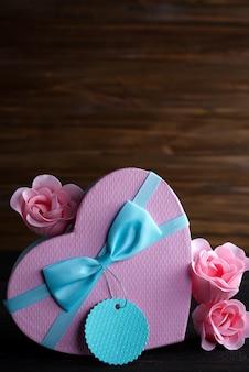 St valentijnsdag vak hart en roze roos op donkere houten achtergrond, kopie ruimte