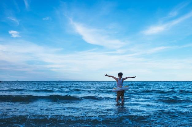 Sta sterk. de jongen die in het midden van de oceaan staat wuift