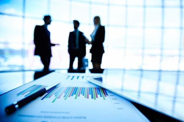 Staafdiagram met silhouetten van collega's achtergrond