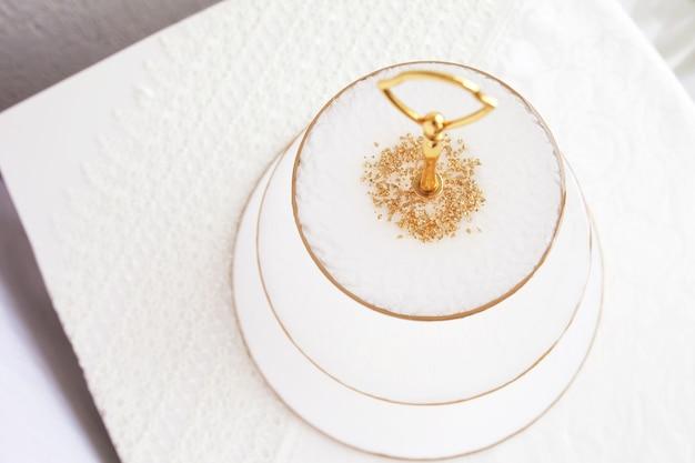 Staan voor snoep en fruit. epoxyhars dienblad. witte vlekken van verf, gouden versiering. onderwerp voor tafelschikking. glans, bezinning. huisdecoratie. bovenaanzicht