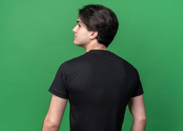 Staand achter het zicht kijkend naar de jonge knappe kerel aan de zijkant met een zwart t-shirt geïsoleerd op een groene muur