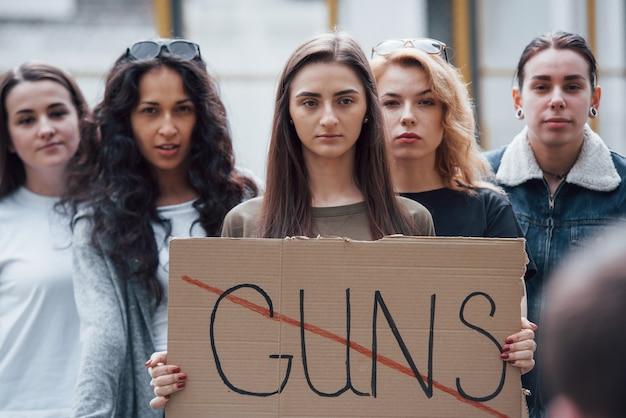 Staand op straat. een groep feministische vrouwen protesteert buitenshuis voor hun rechten
