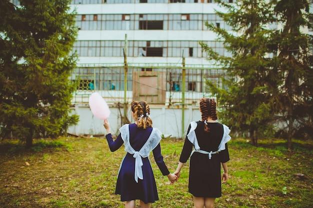 Staand schoolmeisje met typisch navy wit uniform schort suikerspin