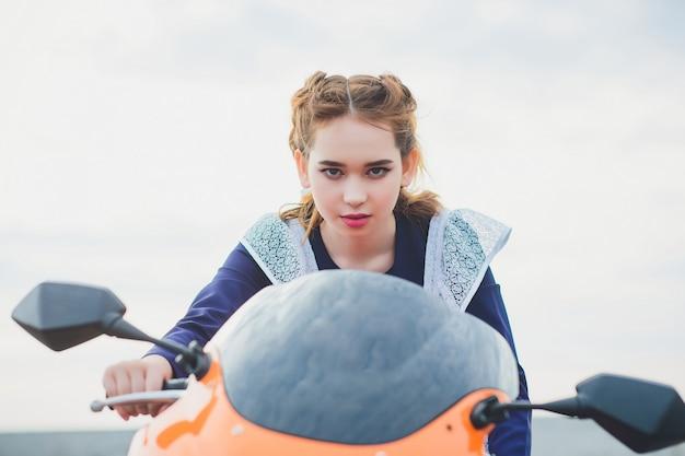 Staand schoolmeisje met typisch navy wit uniform schort zit op motorfiets