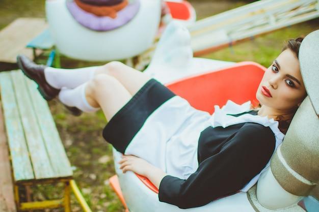 Staand schoolmeisje met typisch navy wit uniform schort