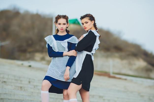 Staand schoolmeisje met typisch navy wit uniform schort Premium Foto