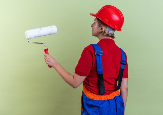 Staande achter het zicht jonge bouwvrouw in uniform met rolborstel geïsoleerd op olijfgroene muur met kopieerruimte