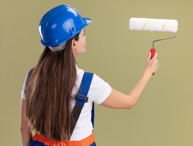 Staande achter mening jonge bouwersvrouw in uniforme holdingsrolborstel die op olijfgroene muur wordt geïsoleerd