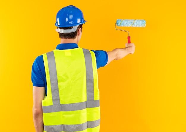 Staande achter weergave jonge bouwer man in uniform met rolborstel geïsoleerd op gele muur met kopieerruimte