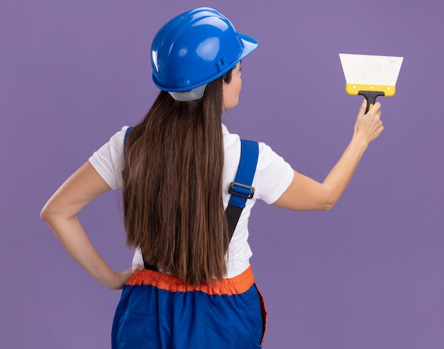 Staande achter weergave jonge bouwer vrouw in uniform houden plamuurmes geïsoleerd op paarse muur