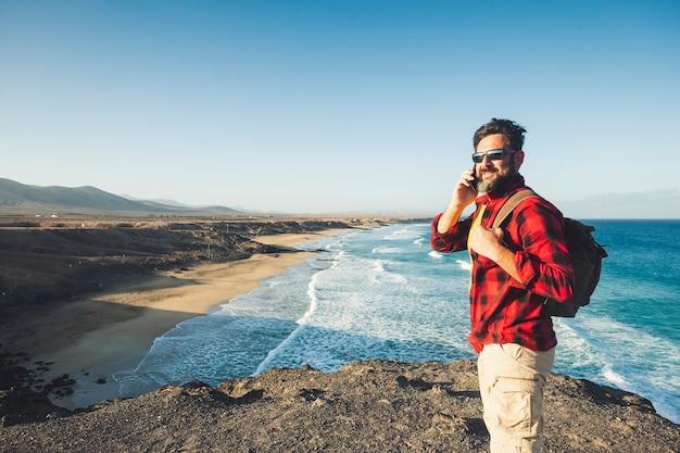 Staande blanke man bellen op de telefoon op een geïsoleerde klif met uitzicht op de golven van de oceaan