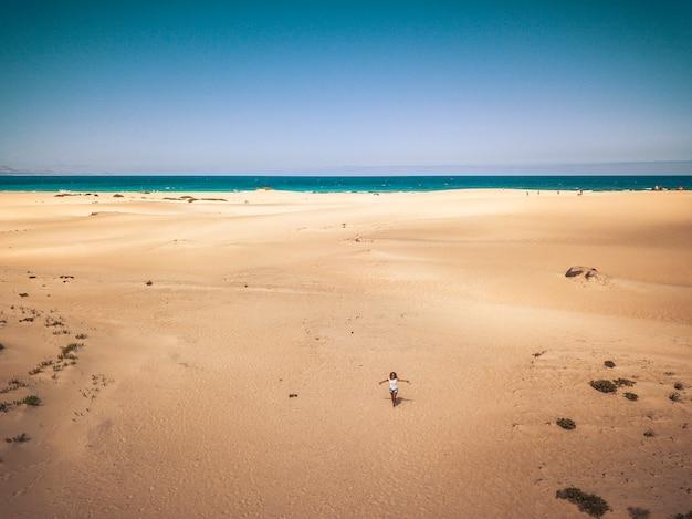 Staande gelukkige meid op het strand met oceaan - concept van reizen en genieten van de natuuractiviteiten in de buitenlucht