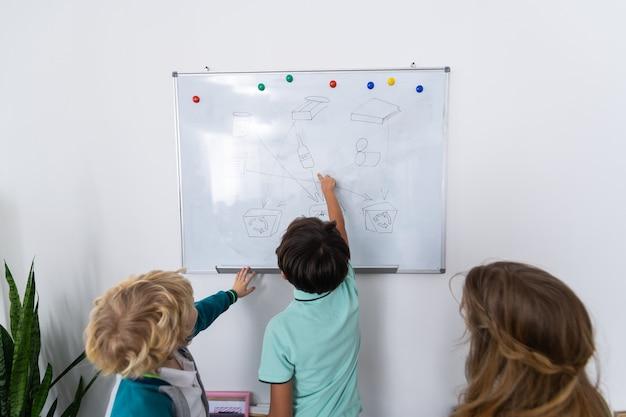 Staande in de buurt van whiteboard. drie leerlingen die bij het whiteboard staan terwijl ze afvalsortering op school bestuderen
