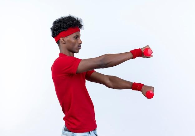 Staande in profiel bekijken jonge afro-amerikaanse sportieve man met hoofdband en polsbandje met halters aan de zijkant geïsoleerd op wit