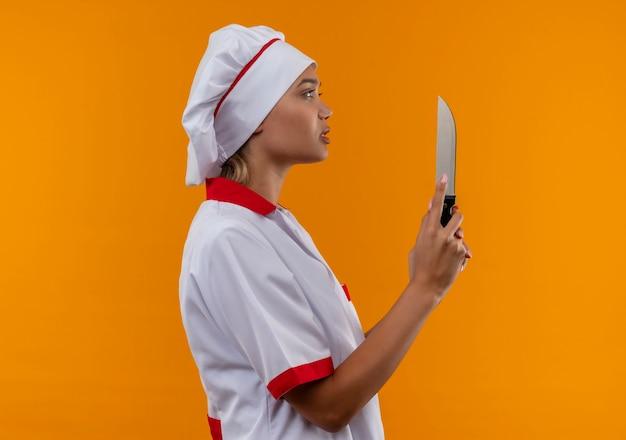Staande in profiel bekijken jonge kok vrouwelijke chef-kok uniform houden mes op geïsoleerde oranje achtergrond met kopie ruimte dragen