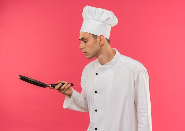 Staande in profiel bekijken jonge mannelijke kok die eenvormige chef-kok draagt die koekenpan in zijn hand met exemplaarruimte bekijkt