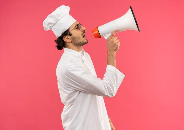 Staande in profiel bekijken jonge mannelijke kok die uniforme chef-kok draagt en glazen spreekt op luidspreker die op roze muur wordt geïsoleerd