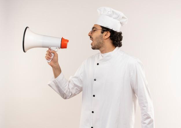 Staande in profiel bekijken jonge mannelijke kok die uniforme chef-kok draagt en glazen spreekt op luidspreker die op witte muur wordt geïsoleerd