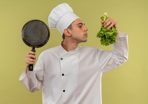 Staande in profiel bekijken jonge mannelijke kok dragen chef-kok uniforme bedrijf koekenpan snuiven salade in zijn hand