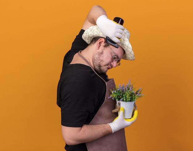 Staande in profiel bekijken jonge mannelijke tuinman tuinieren hoed en handschoenen dragen bloem in bloempot met spray fles geïsoleerd op oranje muur water geven
