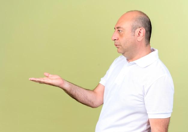 Staande in profiel bekijken volwassen man hand aan kant stak geïsoleerd op olijfgroen