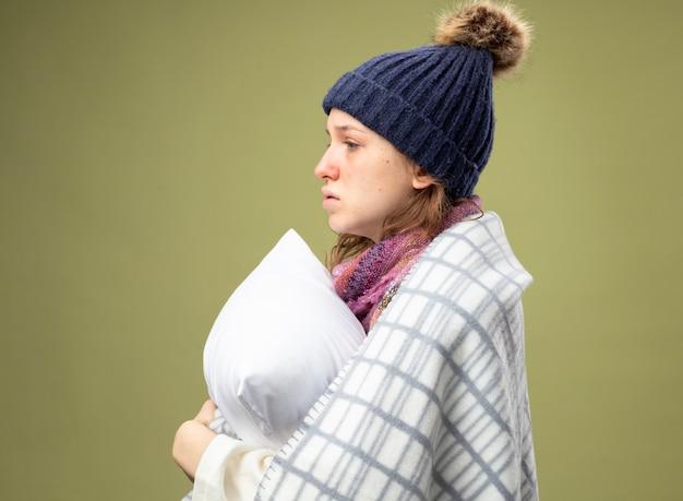 Staande in profiel bekijken ziek meisje dragen witte mantel en winter hoed met sjaal gewikkeld in geruite omhelsde kussen