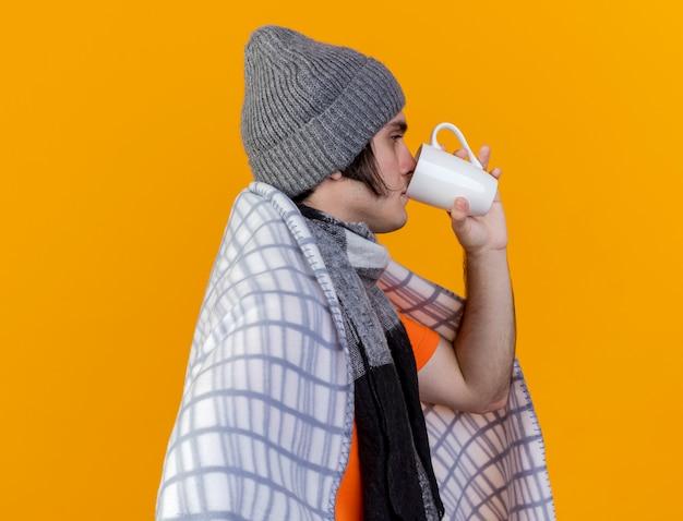 Staande in profiel bekijken zieke jongeman met winter hoed met sjaal gewikkeld in plaid het drinken van thee