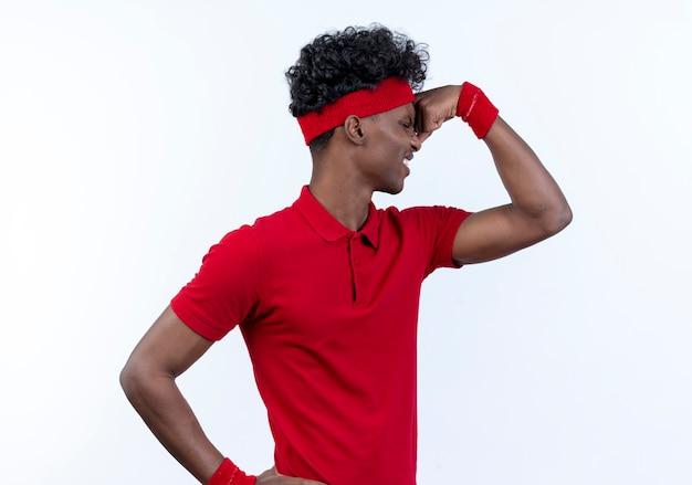 Staande in profiel te bekijken gespannen jonge afro-amerikaanse sportieve man met hoofdband en polsbandje doet sterk gebaar op wit