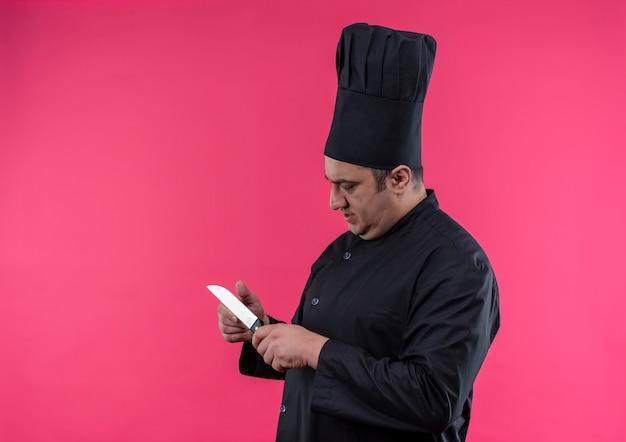 Staande in profiel te bekijken mannelijke kok van middelbare leeftijd in eenvormige chef-kok die mes in zijn hand met exemplaarruimte bekijkt