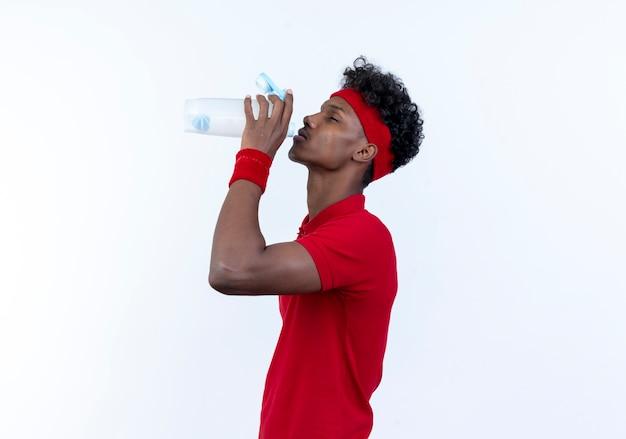 Staande in profiel weergave jonge afro-amerikaanse sportieve man met hoofdband en polsbandje drinkwater uit fles geïsoleerd op wit