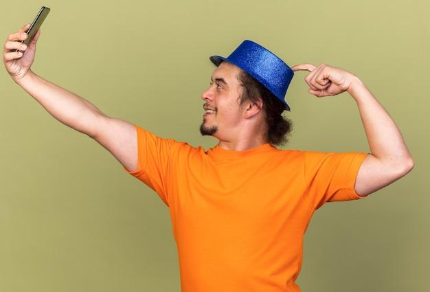 Staande in profiel weergave jonge man met feestmuts nemen een selfie geïsoleerd op olijfgroene muur