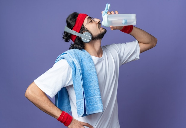 Staande in profiel weergave jonge sportieve man met hoofdband met polsband en handdoek op schouder drink water