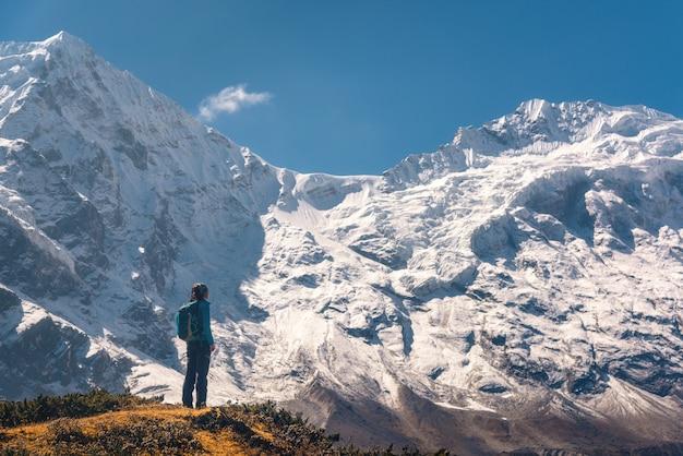 Staande jonge vrouw op de heuvel en kijkend op verbluffende himalaya-bergen