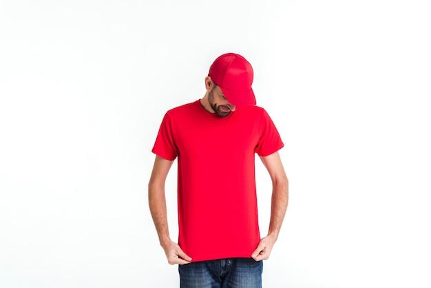 Staande koerier man in rood uniform naar beneden te kijken