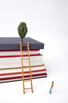 Staande man en houten ladder op stapel nieuwe boeken