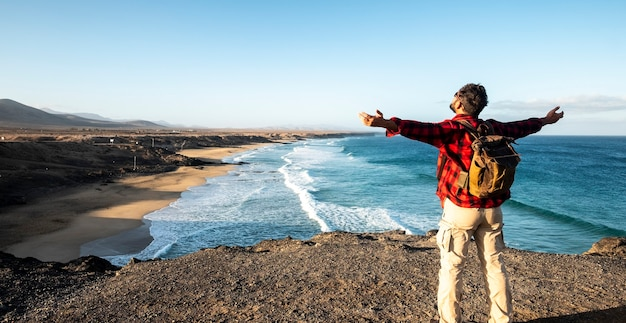 Staande man geniet van het reis- en natuurlandschap voor hem