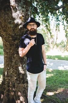 Staande man naast bruine en groene boom