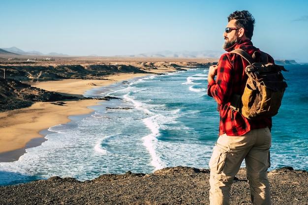 Staande man reiziger mensen kijken en genieten van de bestemming op een prachtig tropisch strand met rotsklif - alternatieve vakantie levensstijl - reislust en rugzakleven