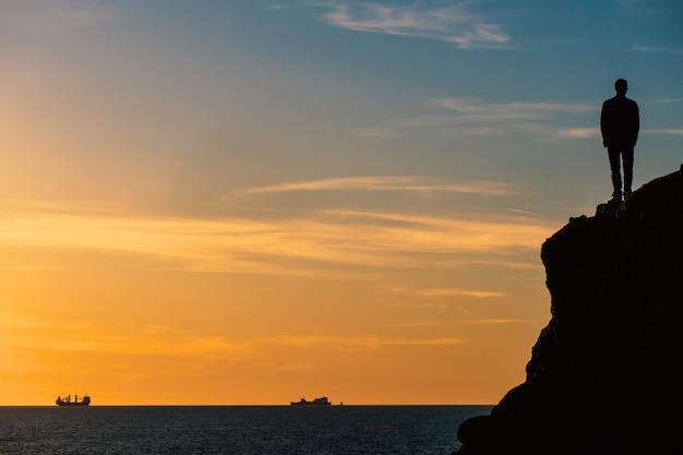Staande man silouette op een rots voor de zee bij zonsondergang