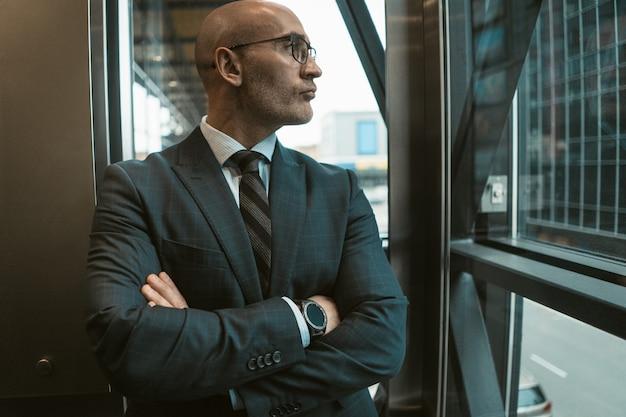 Staande met gevouwen armen kale zakenman in pak en bril wegkijken in het raam van moderne kantoor met uitzicht op straat.