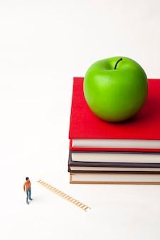 Staande miniatuurmens met appel op stapel nieuwe boeken