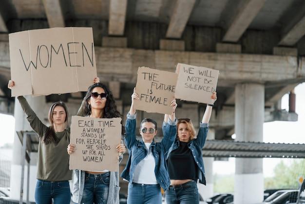 Staande onder de brug. een groep feministische vrouwen protesteert buitenshuis voor hun rechten