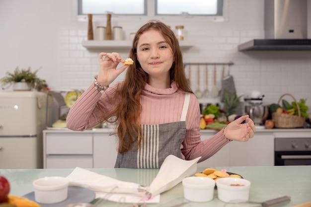 Staande op een bank thuis eet een gelukkig meisje een dieetkoekje.