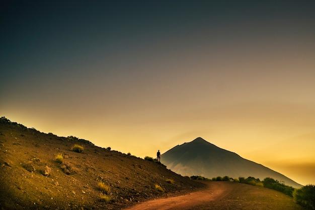 Staande silhouet van man op hoge top berg bij zonsondergang